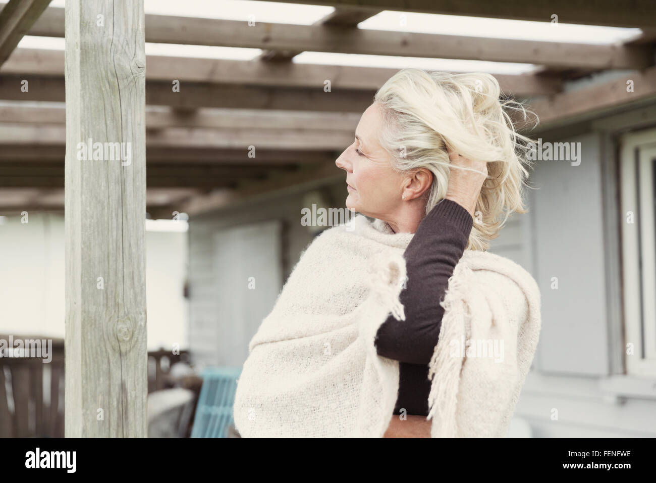 Senior woman with hand in hair wearing shawl on porch - Stock Image