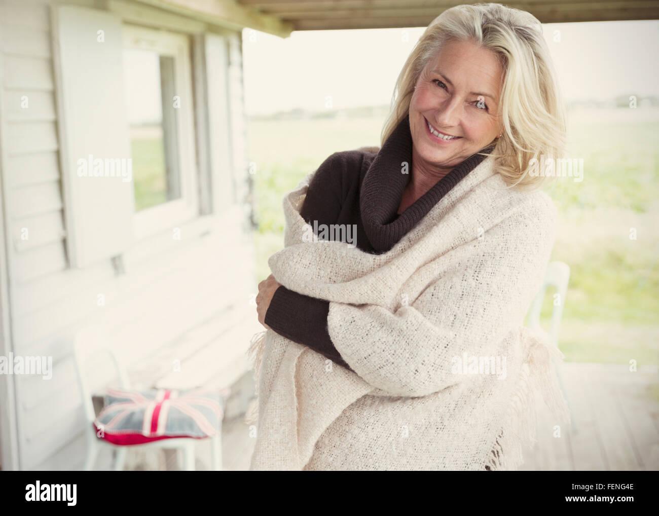 Portrait smiling senior woman wearing shawl on porch - Stock Image
