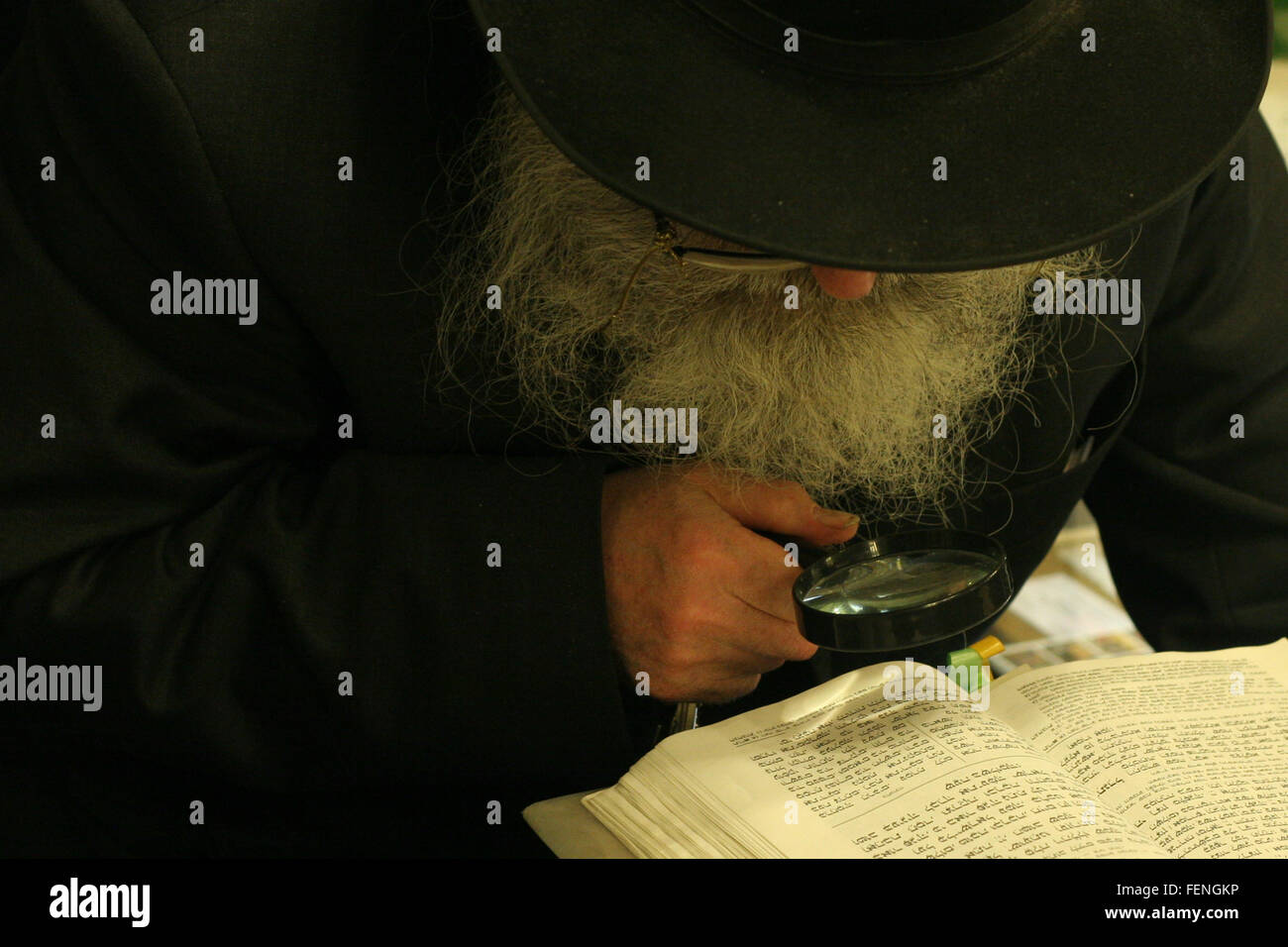 Detective Reading Book Through Magnifying Glass - Stock Image