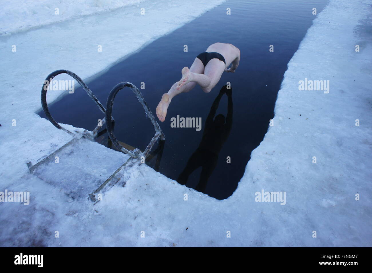 Full Length Of Man Diving In Frozen Swimming Pool - Stock Image