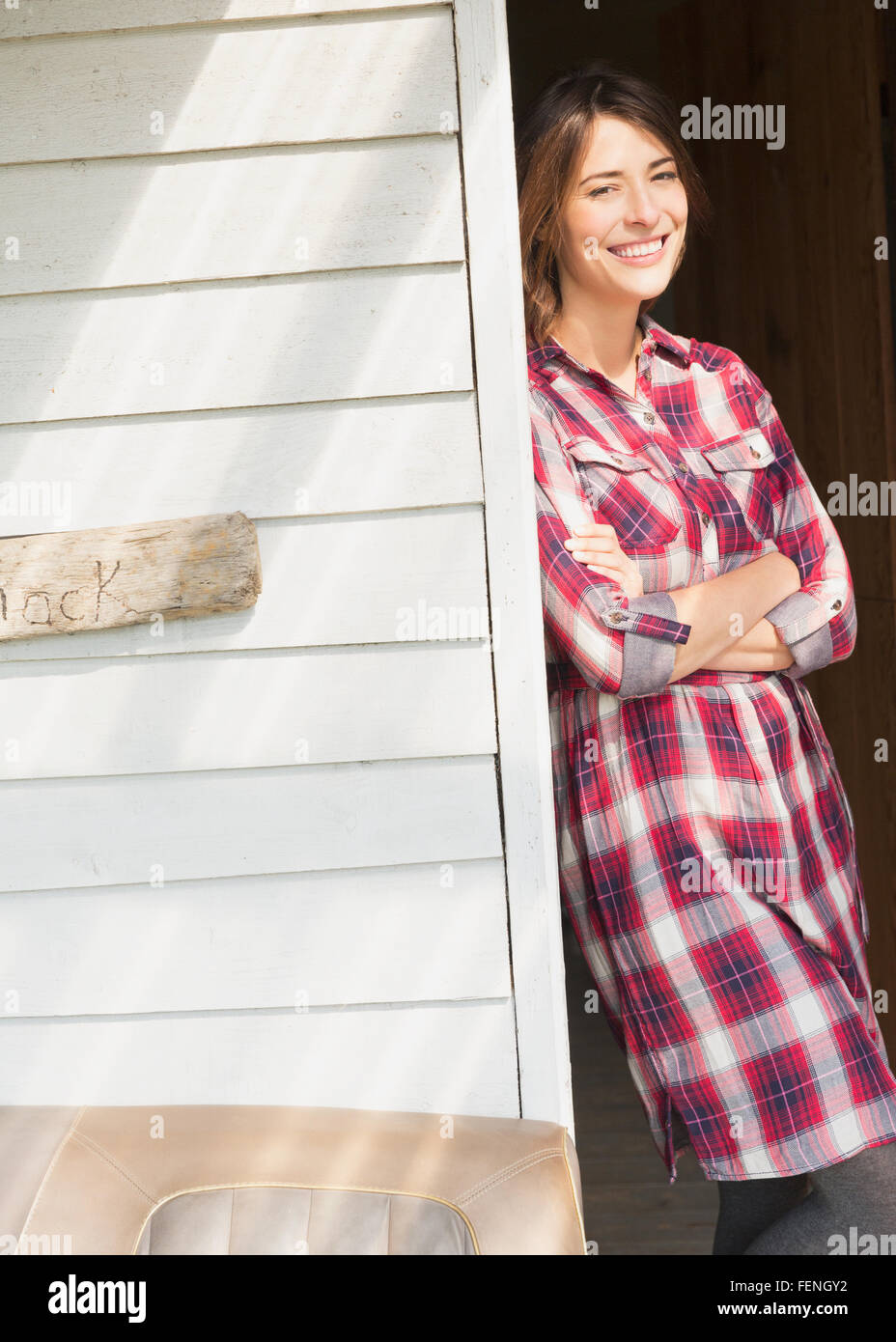 Portrait smiling brunette woman in plaid dress in sunny doorway - Stock Image
