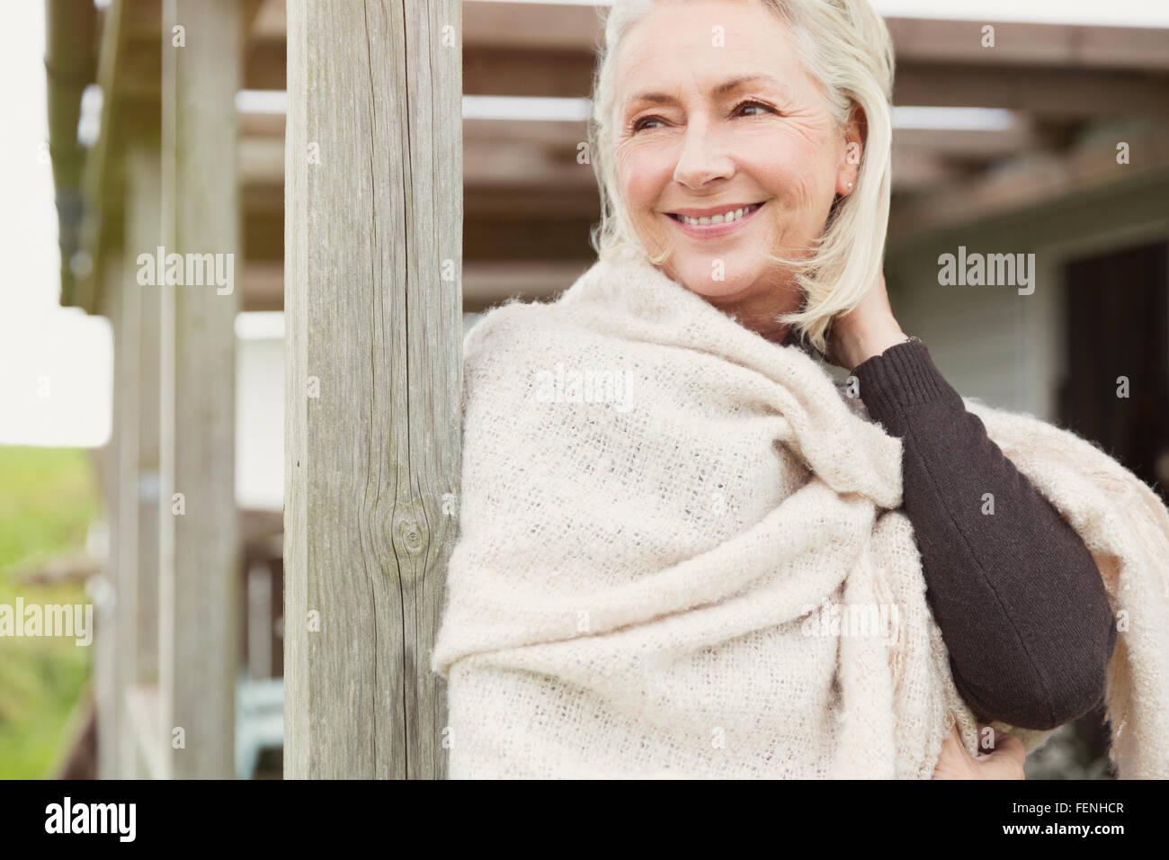 Smiling senior woman wearing shawl on porch - Stock Image