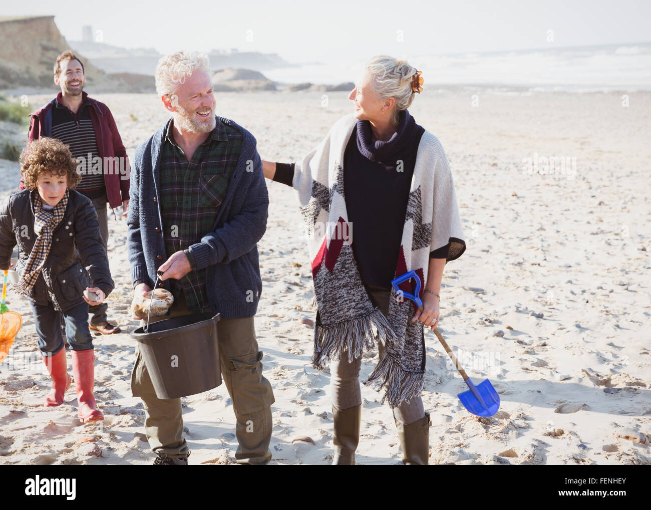 Multi-generation family clam digging on beach - Stock Image