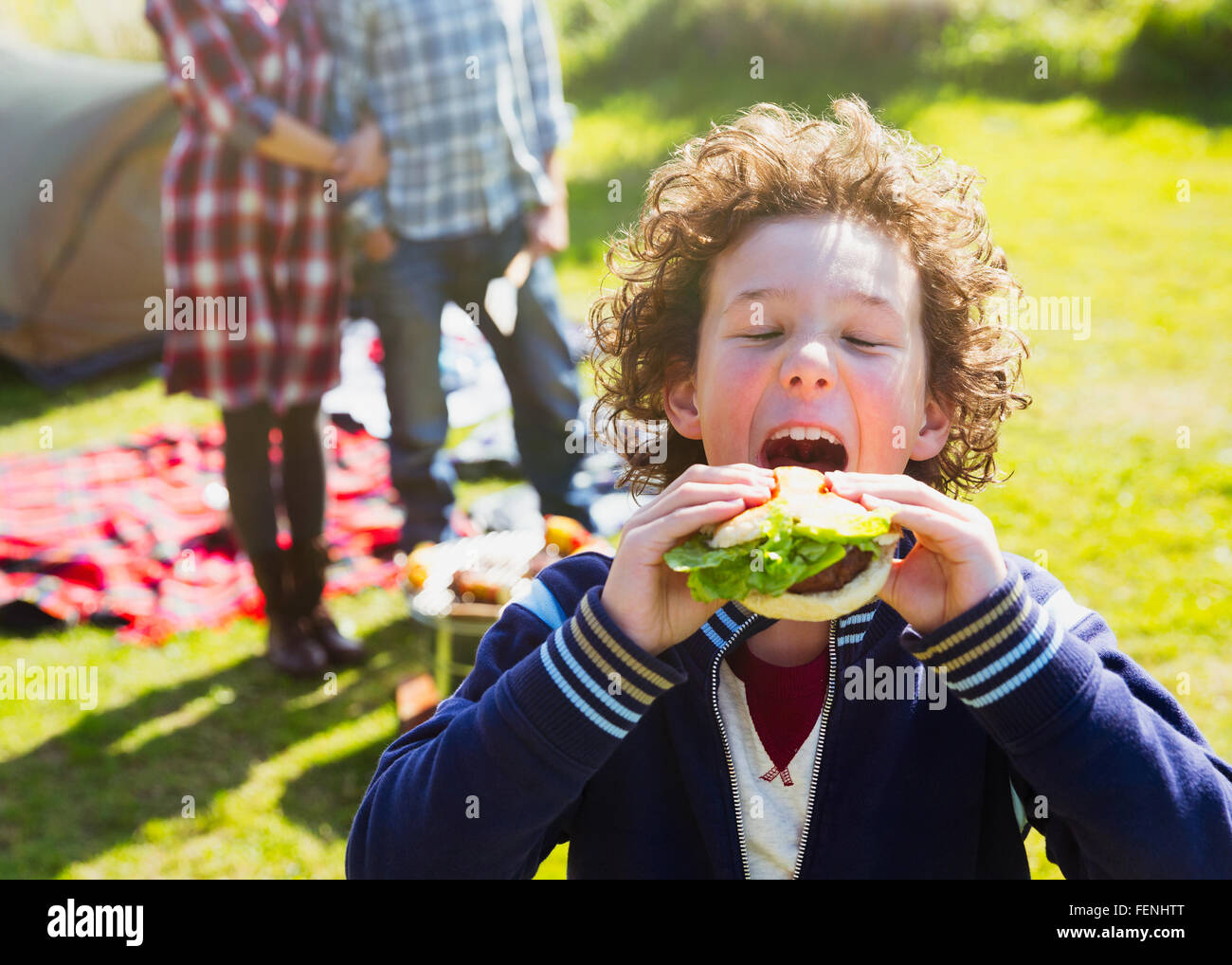 Enthusiastic boy taking large bite of hamburger at sunny campsite - Stock Image