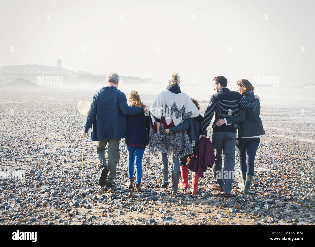 Multi-generation family walking in a row on beach - Stock Image