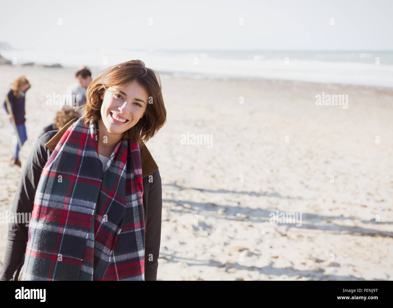 Portrait smiling woman in plaid scarf on sunny beach - Stock Image