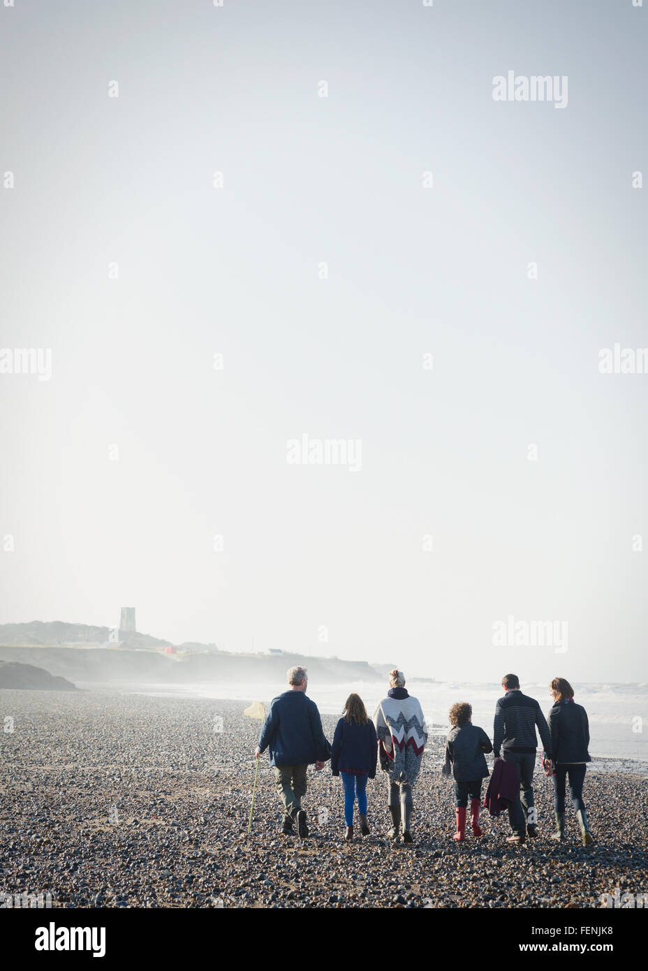 Multi-generation family walking on sunny beach in a row - Stock Image