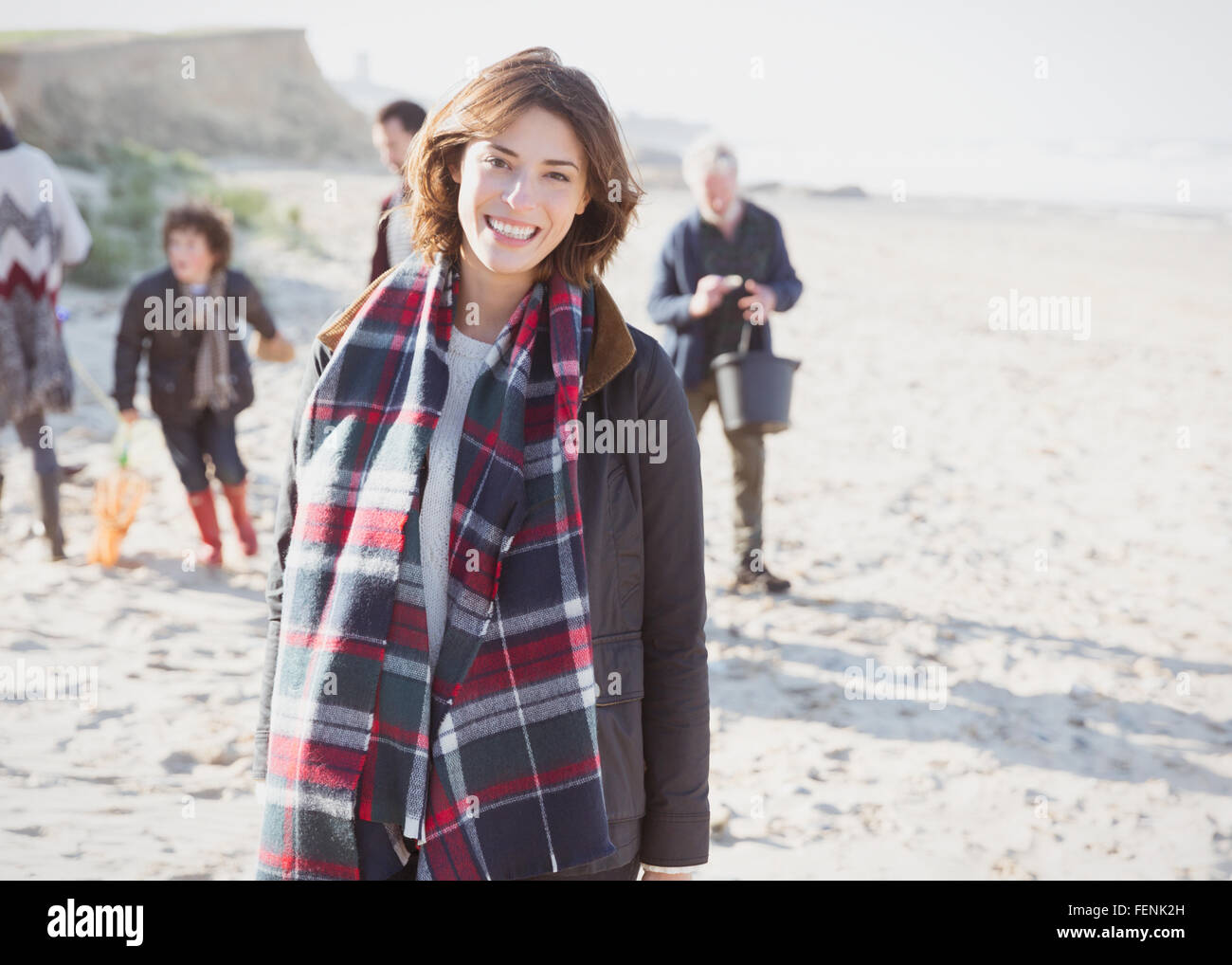 Portrait smiling woman in plaid scarf with family on beach - Stock Image