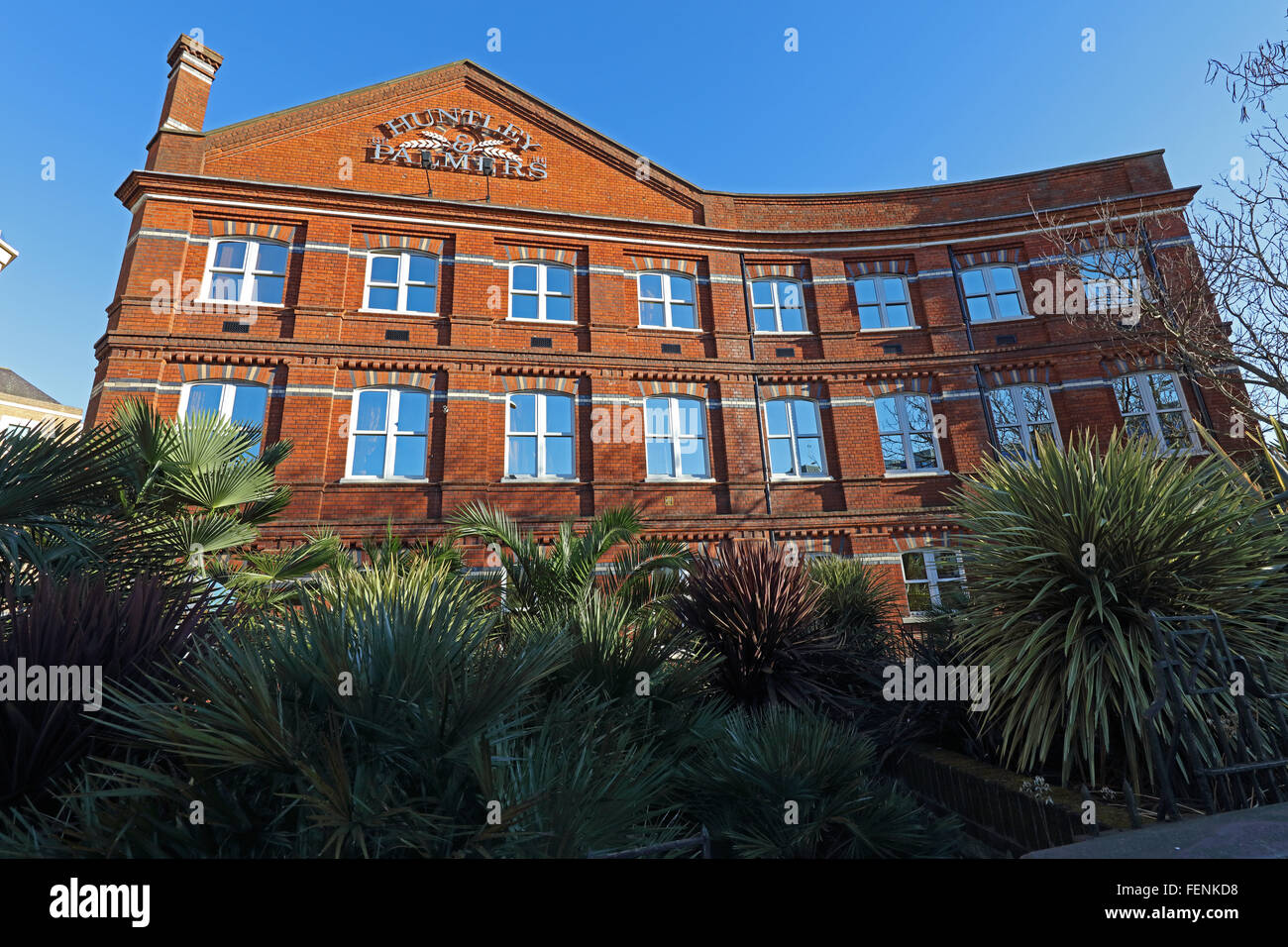 The front of the Huntley and Palmer's building, built in red brick with a chimney at one end and many windows - Stock Image