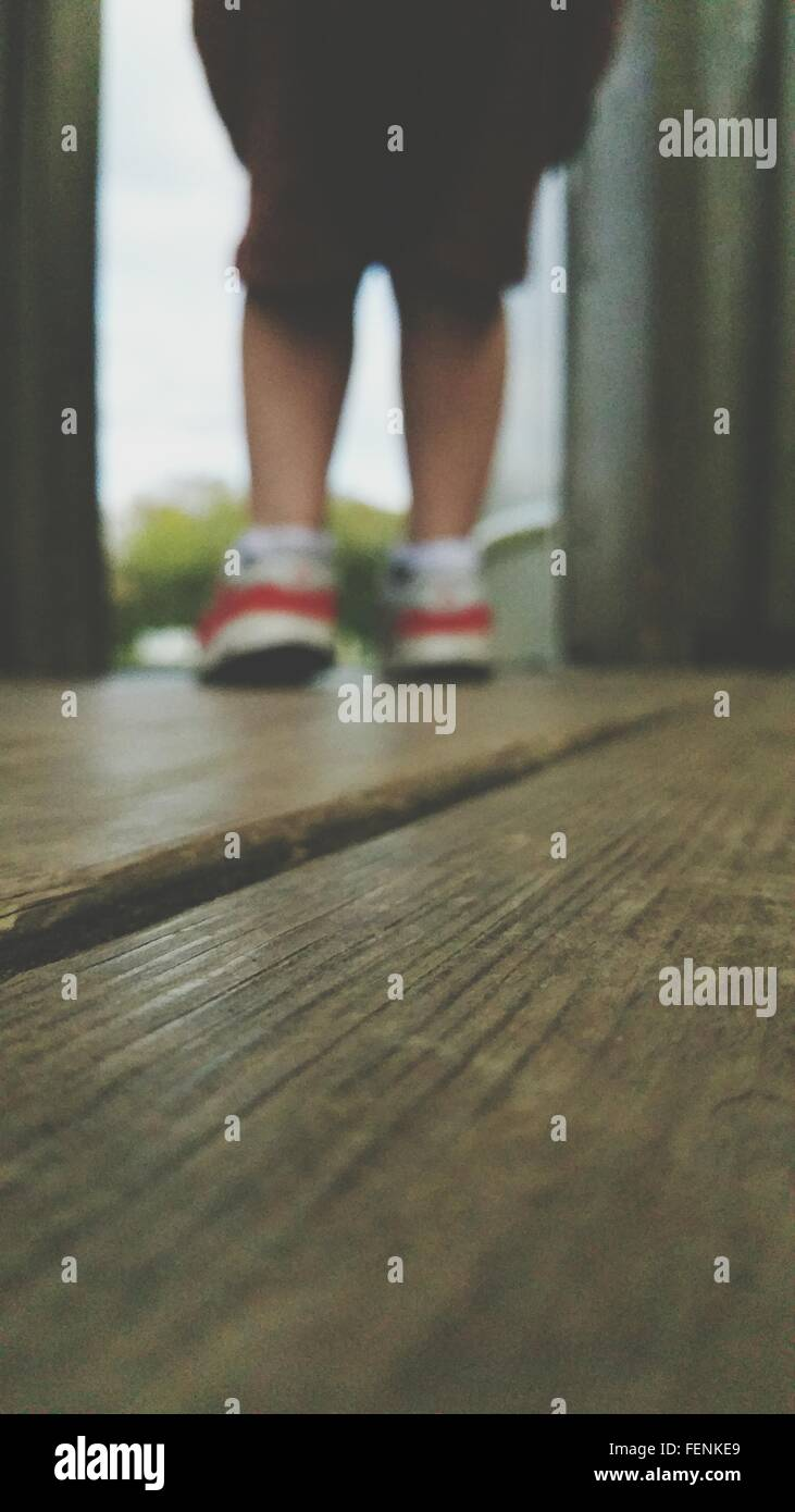 Boy Standing On Wooden Floor - Stock Image