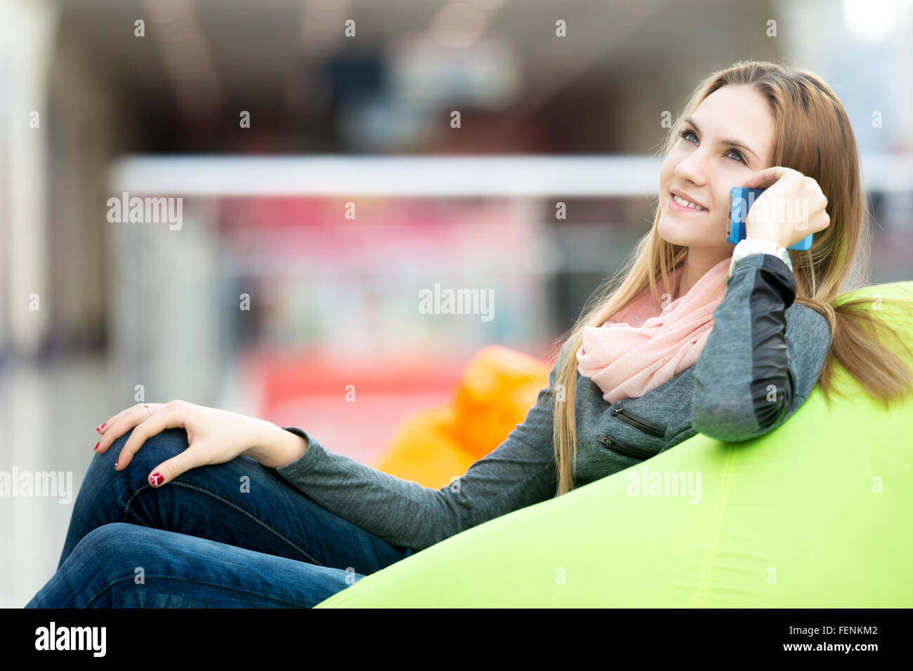 Dreamily smiling young woman in casual style clothes sitting on bean bag in office or shopping center, leisure area - Stock Image