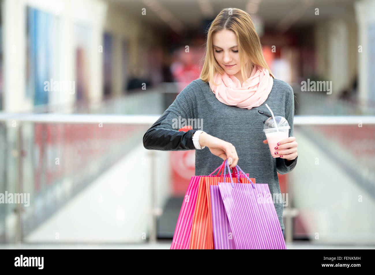 Young shopper woman looking at her watch while carrying paper bags with purchases and milkshake - Stock Image