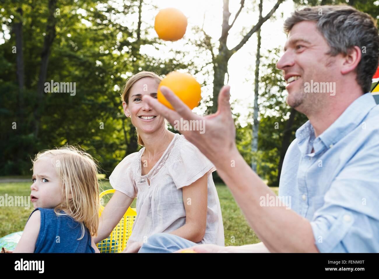 Mature man juggling oranges at family picnic in park - Stock Image