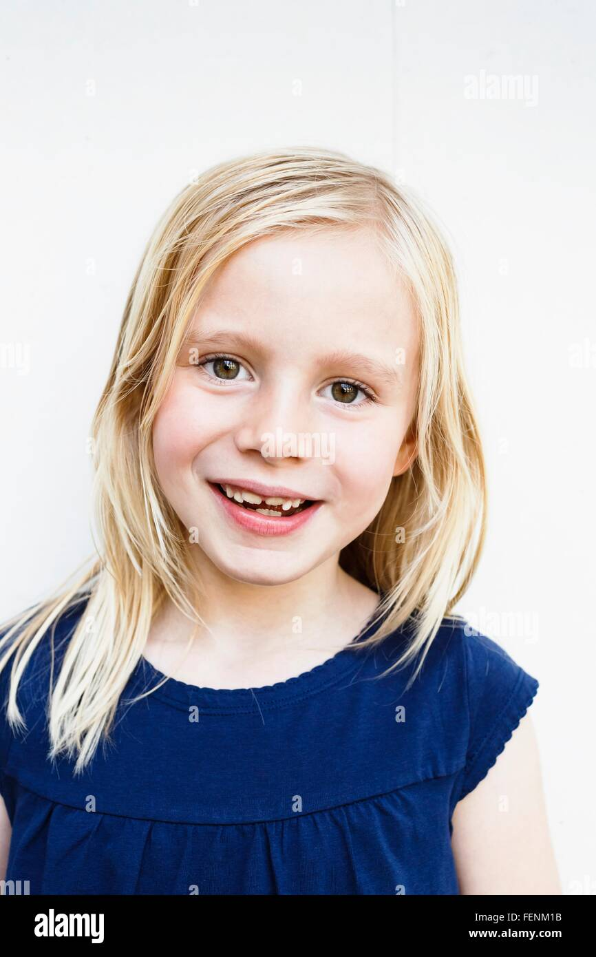 Portrait of cute girl with toothy grin in front of white wall - Stock Image
