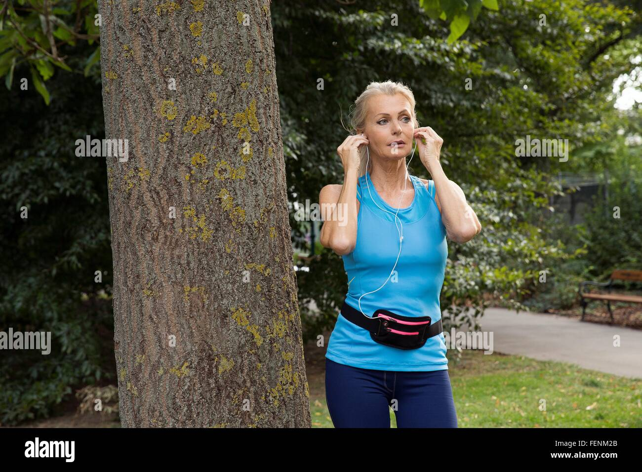 Mature woman adjusting earphones whilst training in park - Stock Image