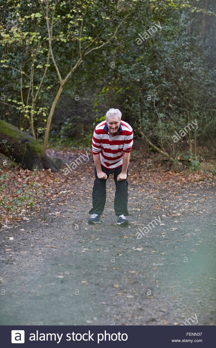 Exhausted mature male runner stopping to catch his breath on forest track - Stock Image