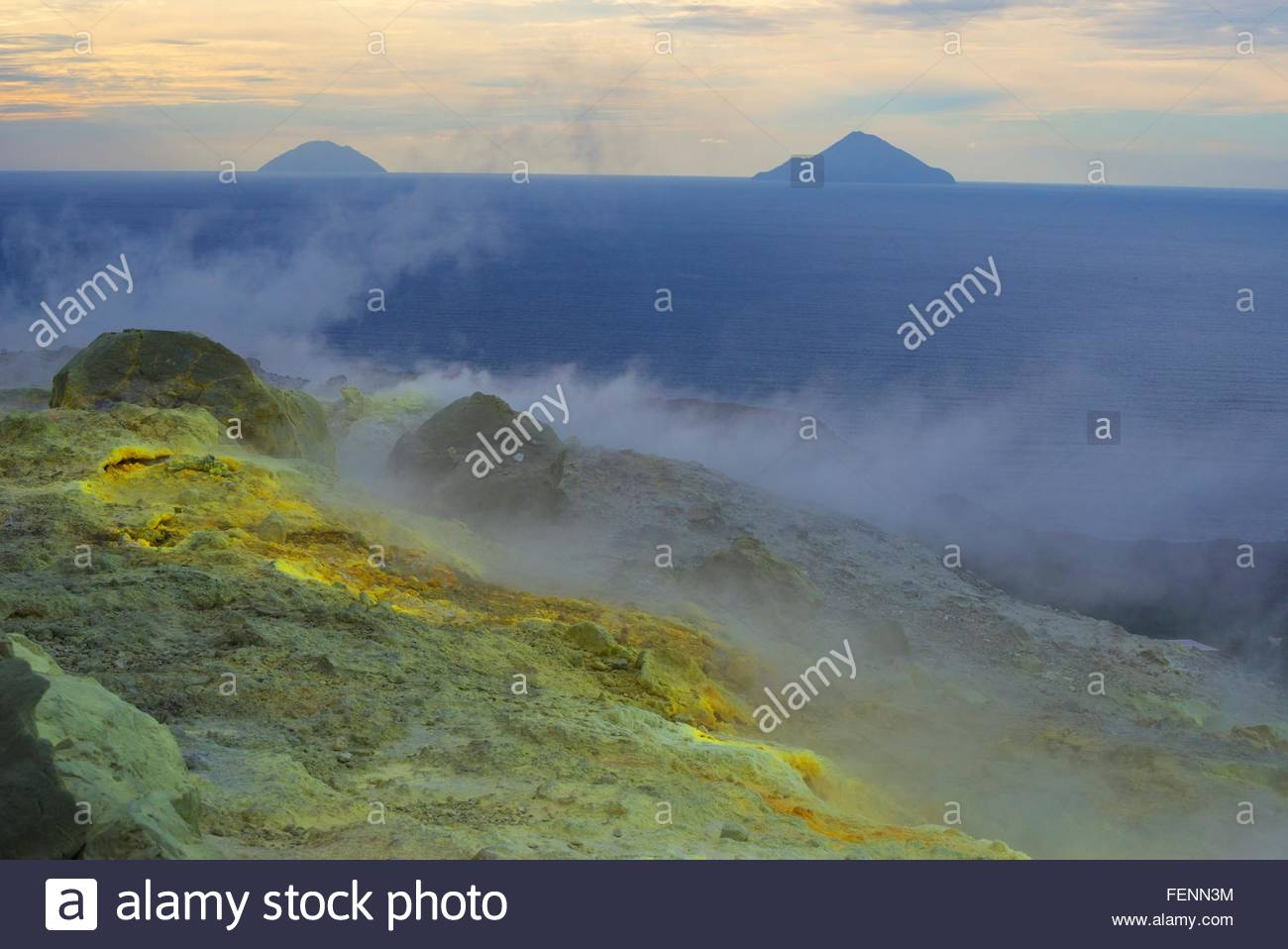 Sulphur and fumarole smoke at Gran Cratere and view of islands, Vulcano Island, Aeolian Islands, Sicily, Italy - Stock Image