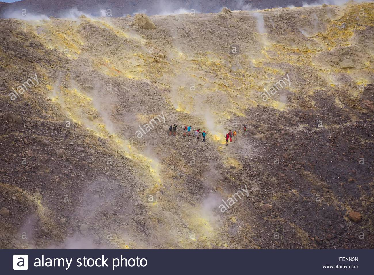 Group of tourists walking through fumarole smoke at Gran Cratere, Vulcano Island, Aeolian Islands, Sicily, Italy - Stock Image