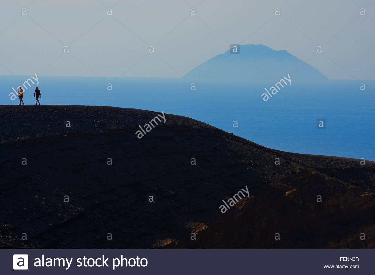 Two silhouetted tourists walking crater rim, Vulcano Island, Aeolian Islands, Sicily, Italy - Stock Image