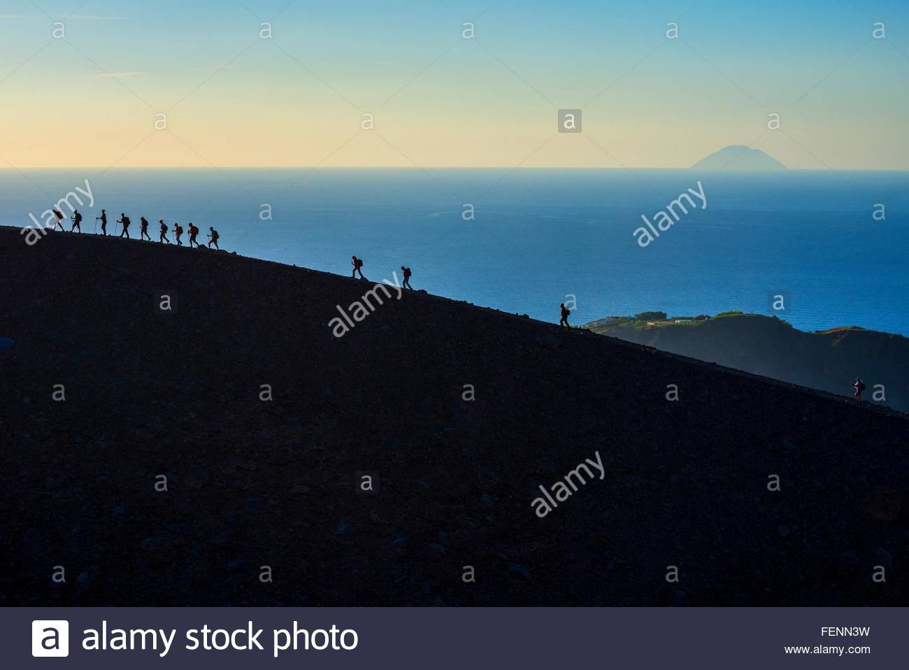 Large group of silhouetted tourists walking rim at Gran Cratere, Vulcano Island, Aeolian Islands, Sicily, Italy - Stock Image