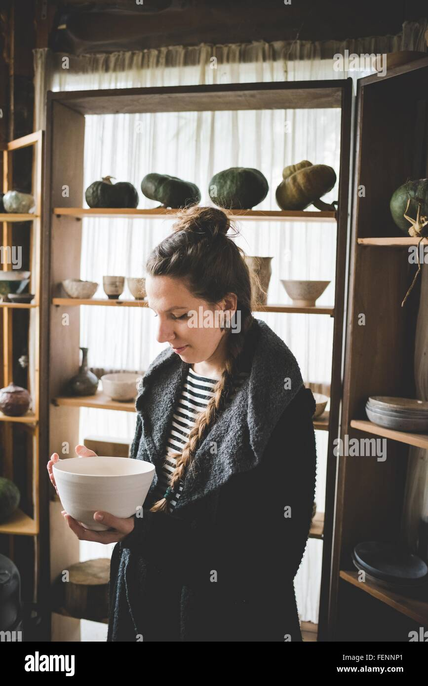 Young woman holding ceramic dish in front of shelves displaying clay pots and pumpkins - Stock Image