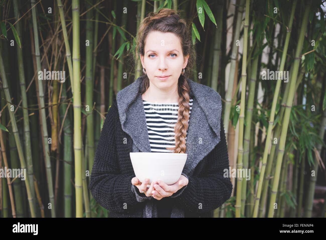 Front view of young woman standing in front of bamboo grove holding ceramic dish looking at camera - Stock Image