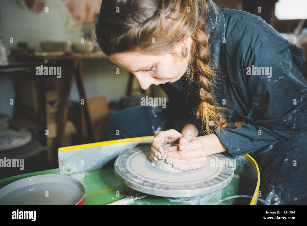 Young woman with plaited hair using pottery wheel - Stock Image