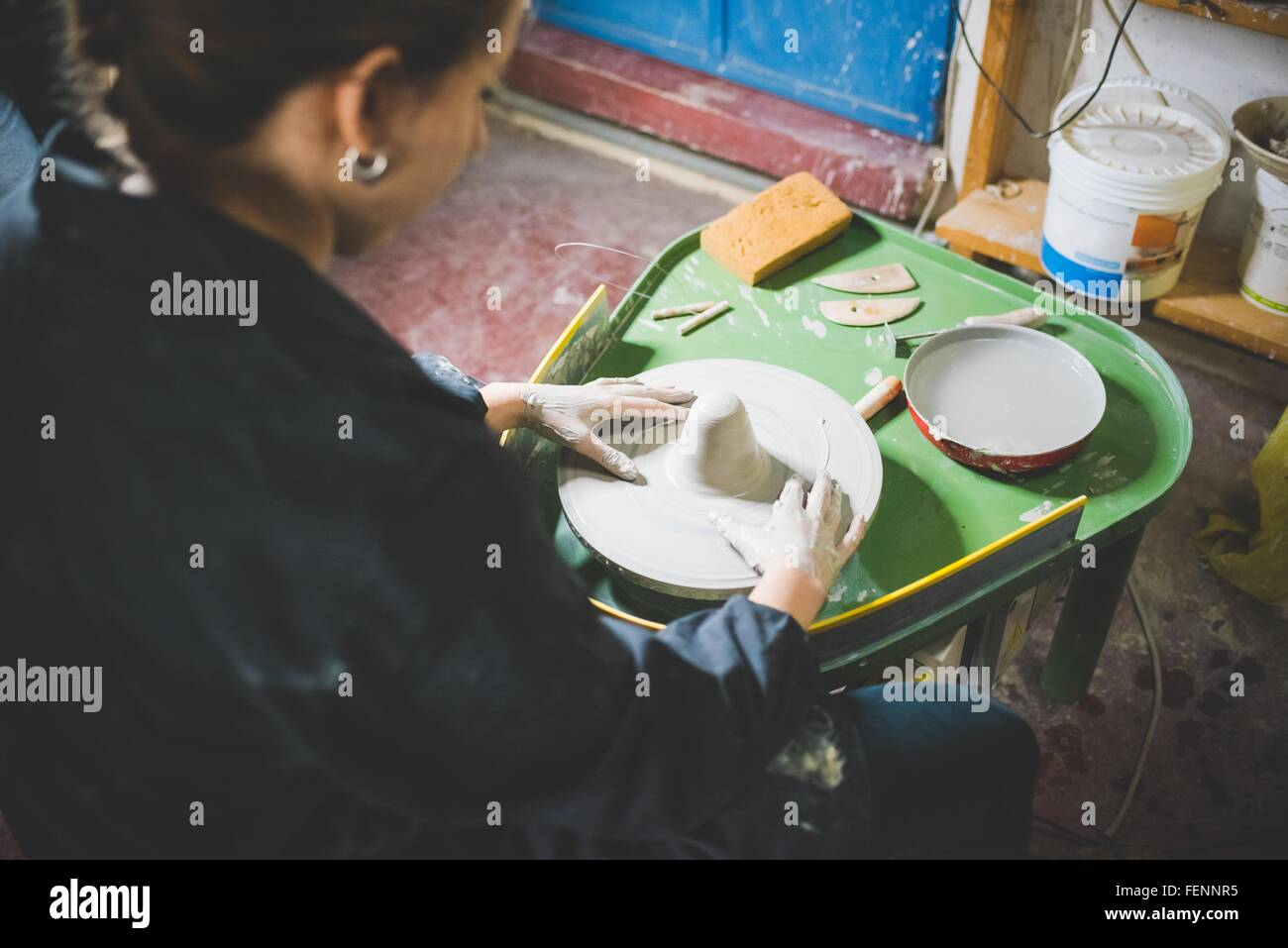 Over shoulder view of young woman sitting using pottery wheel - Stock Image