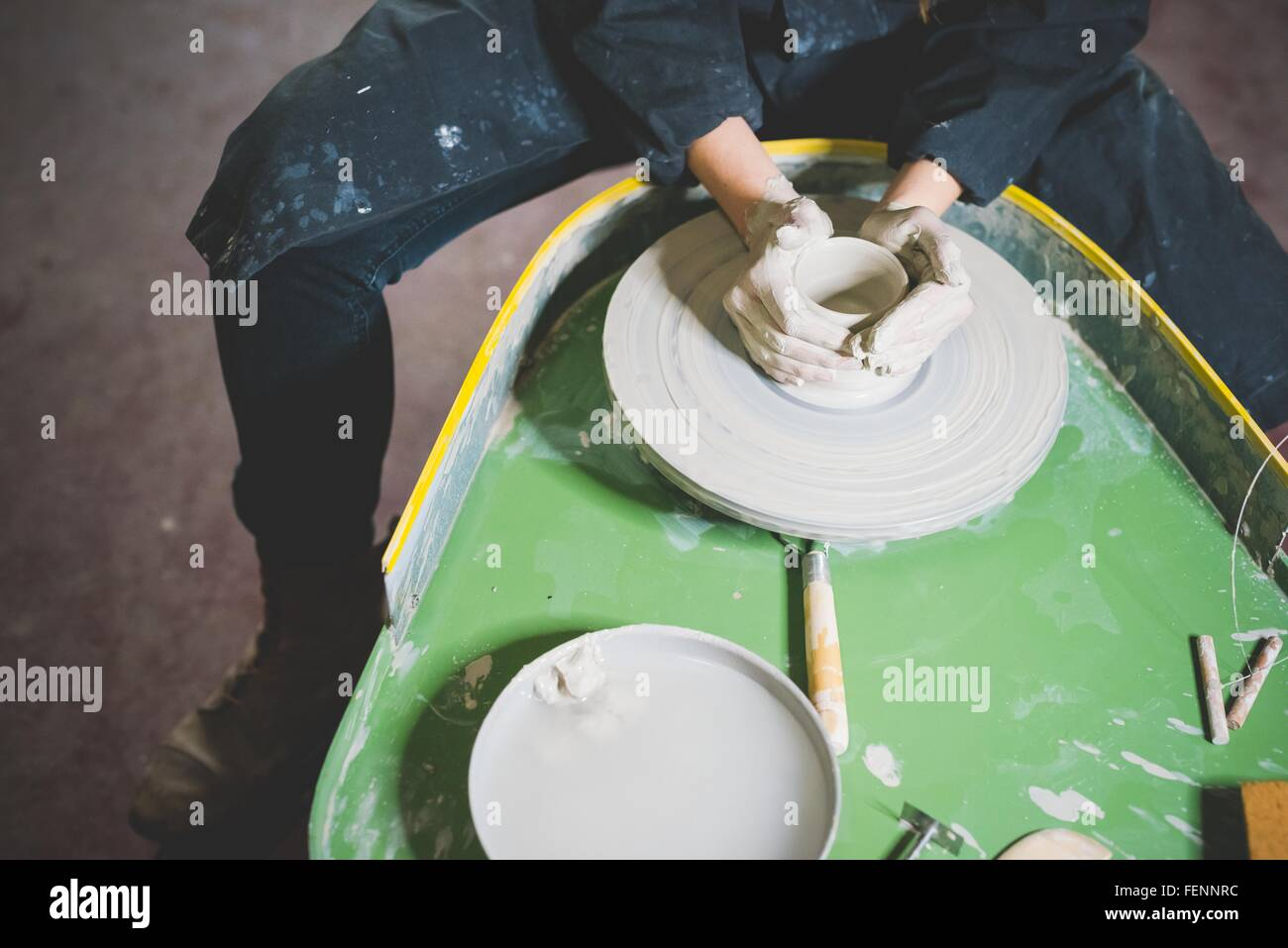High angle view of young woman, waist down, sitting at pottery wheel making clay pot - Stock Image