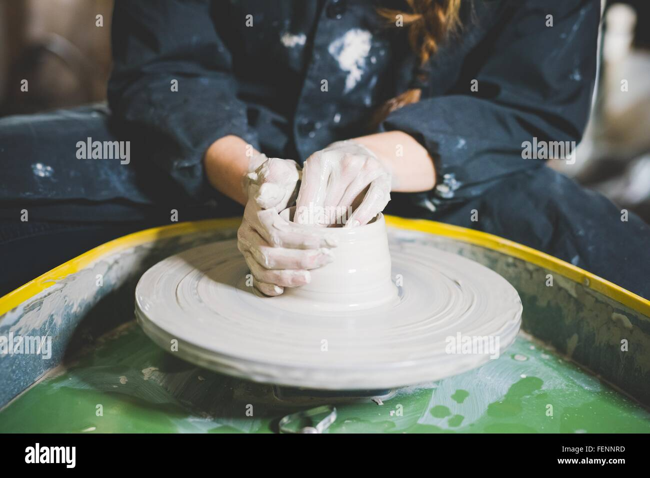 Cropped view of young woman sitting at pottery wheel making clay pot - Stock Image