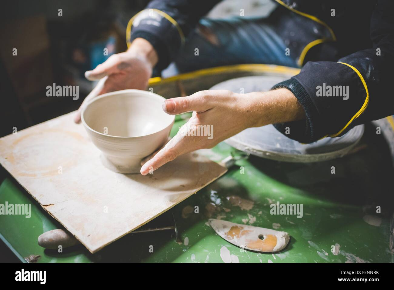 Cropped view of mid adult man sitting at potters wheel holding clay pot - Stock Image
