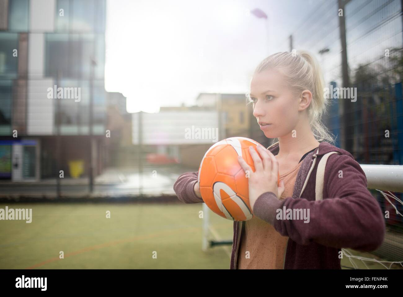 Young woman about to throw football - Stock Image