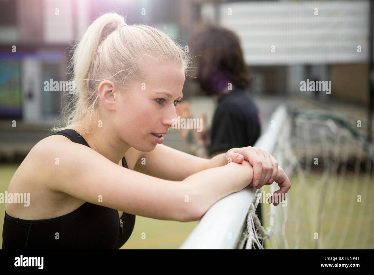 Young woman taking a break, leaning on football goal - Stock Image