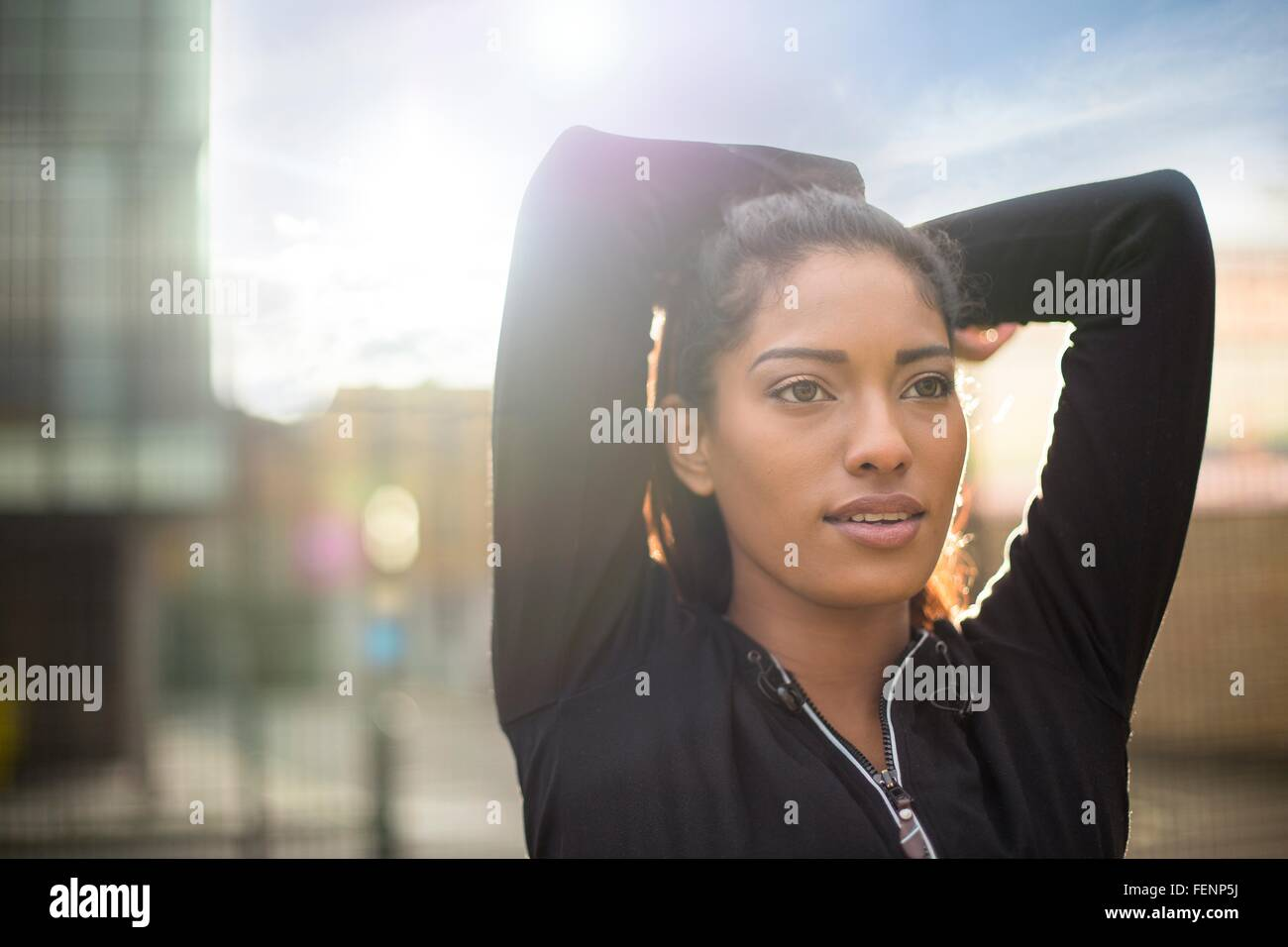 Portrait of young woman stretching, arms behind head - Stock Image