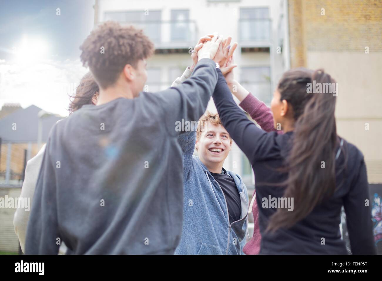 Group of adults, touching hands, outdoors - Stock Image