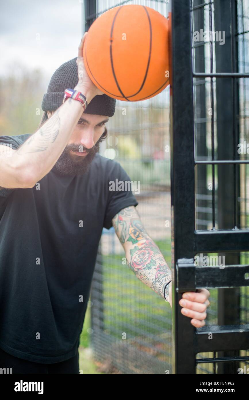 Mid adult man standing by fence, holding basketball against fence, pensive expression - Stock Image