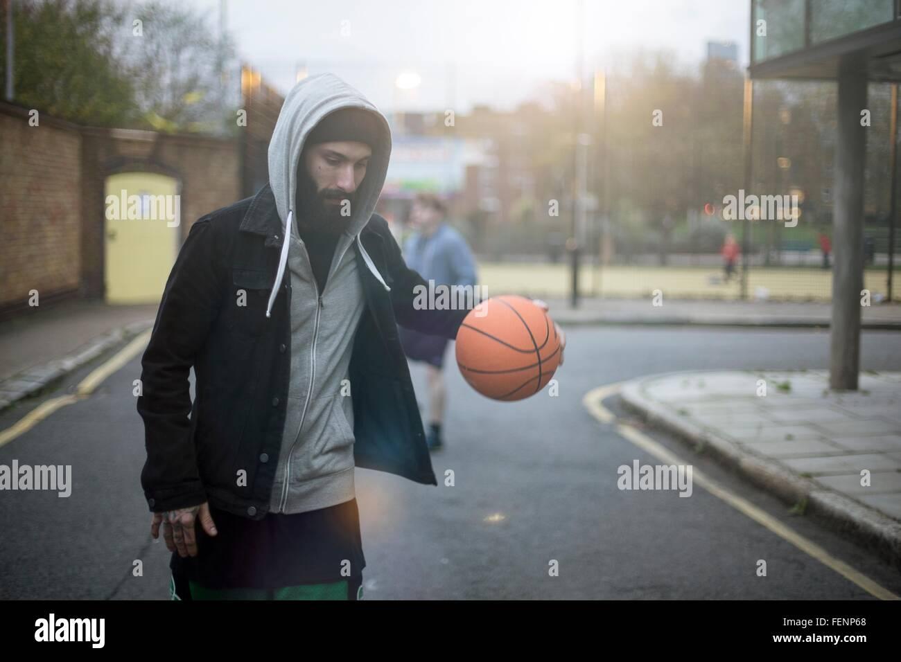 Mid adult man walking along street, bouncing basketball - Stock Image