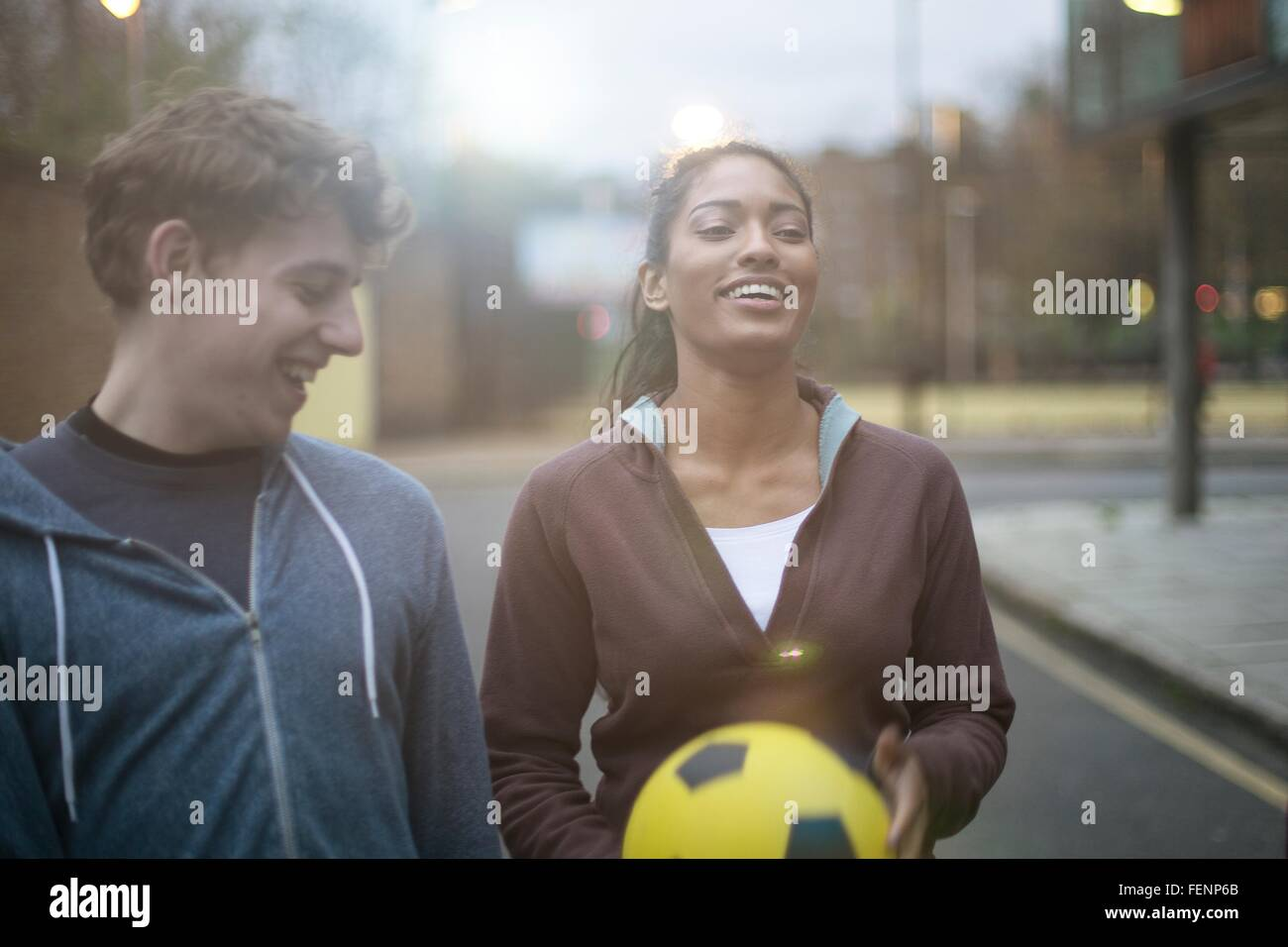 Young man and woman walking in street, holding football - Stock Image