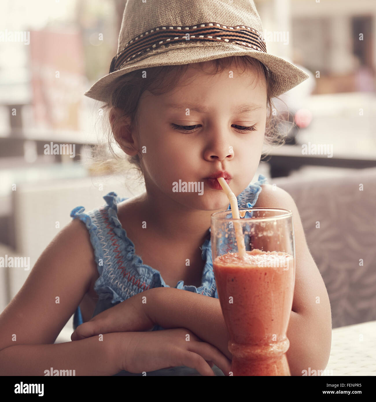 Fun kid girl in hat drinking smoothie juice from glass in street city cafe. Toned closeup portrait - Stock Image