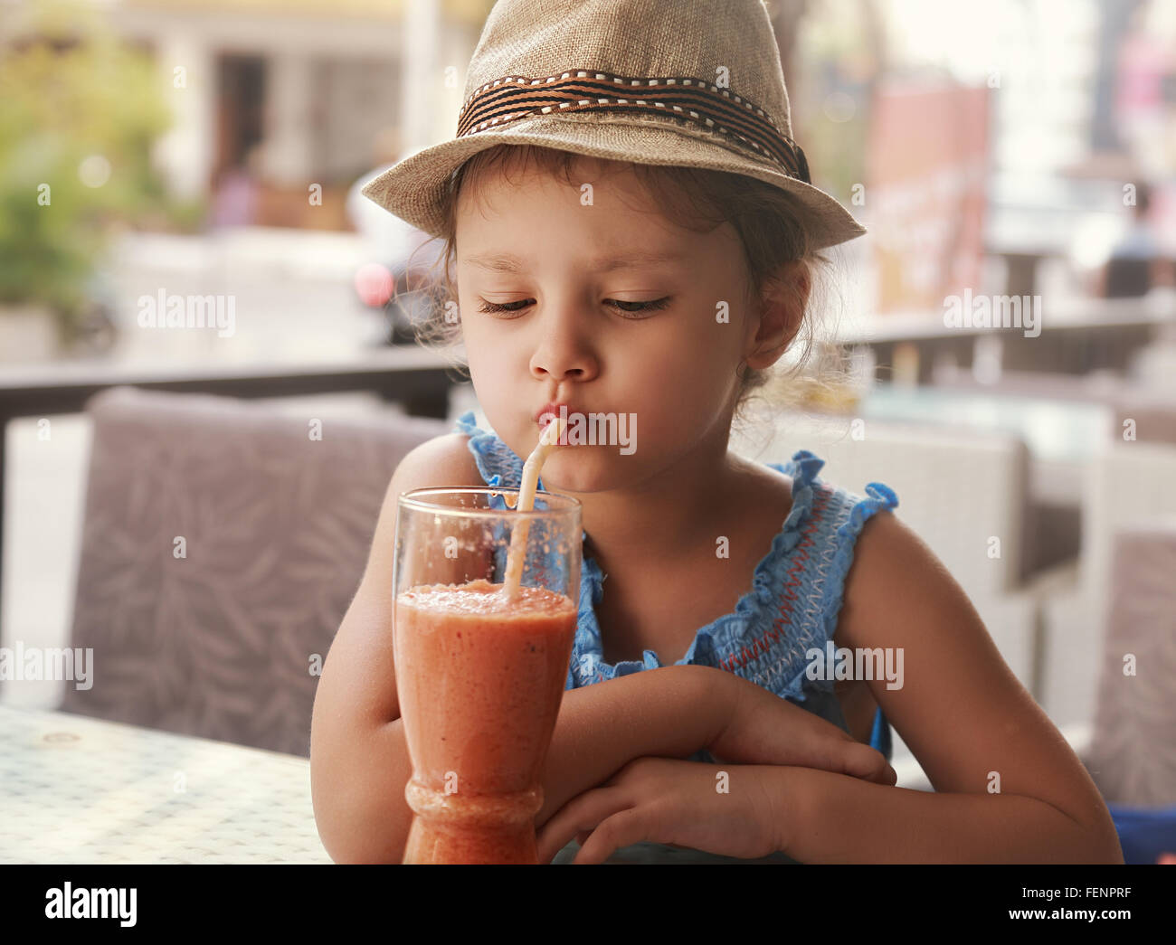 Fun kid girl in hat drinking smoothie juice from glass in street city cafe - Stock Image
