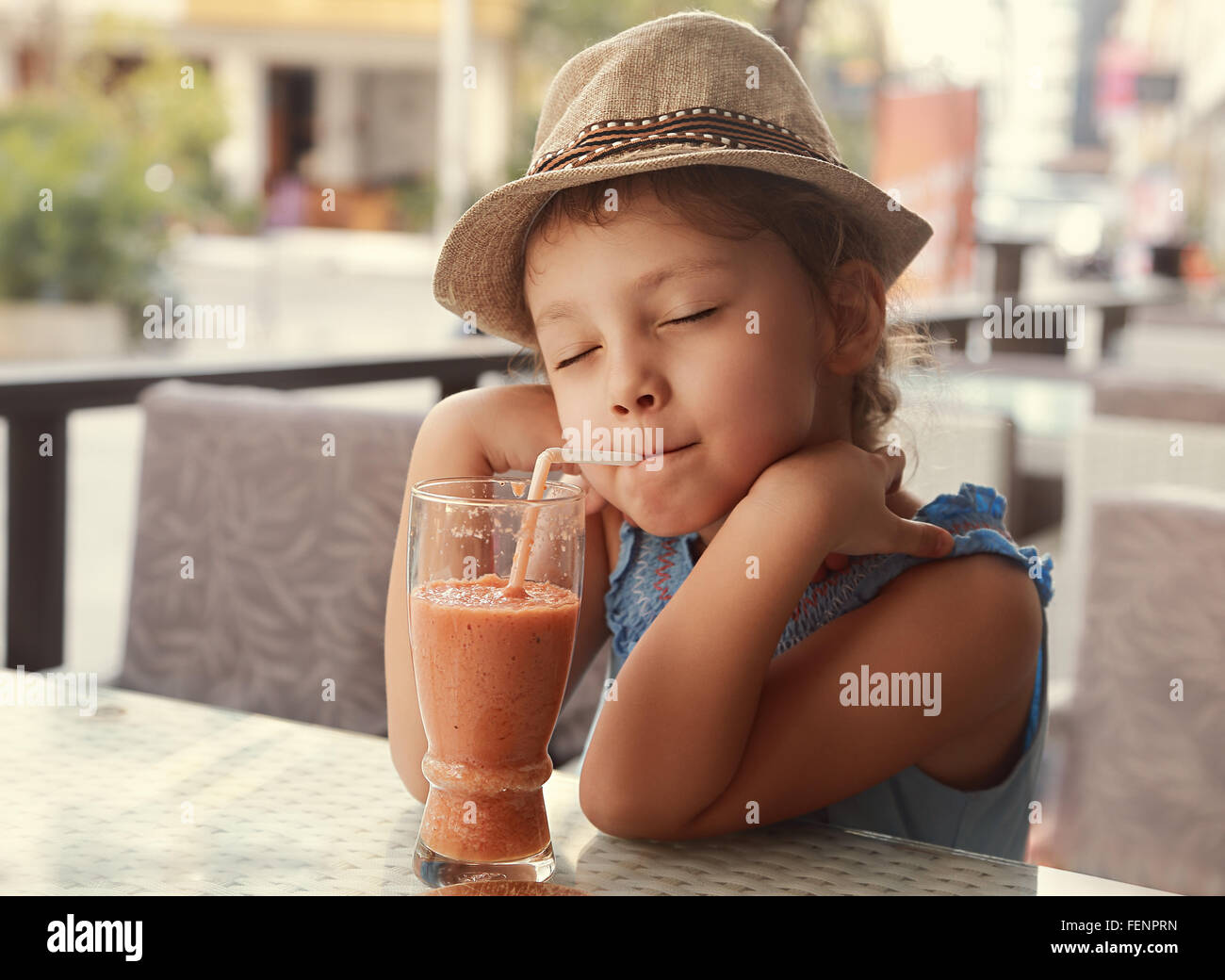 Happy enjoying kid girl drinking tasty natural smoothie juice with closed relaxed eyes in street restaurant - Stock Image