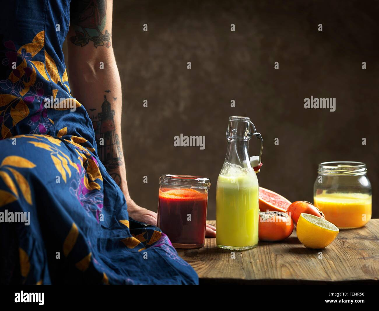 Cropped view of  woman wearing dress sitting on table with raw juices in glass bottle and jars - Stock Image