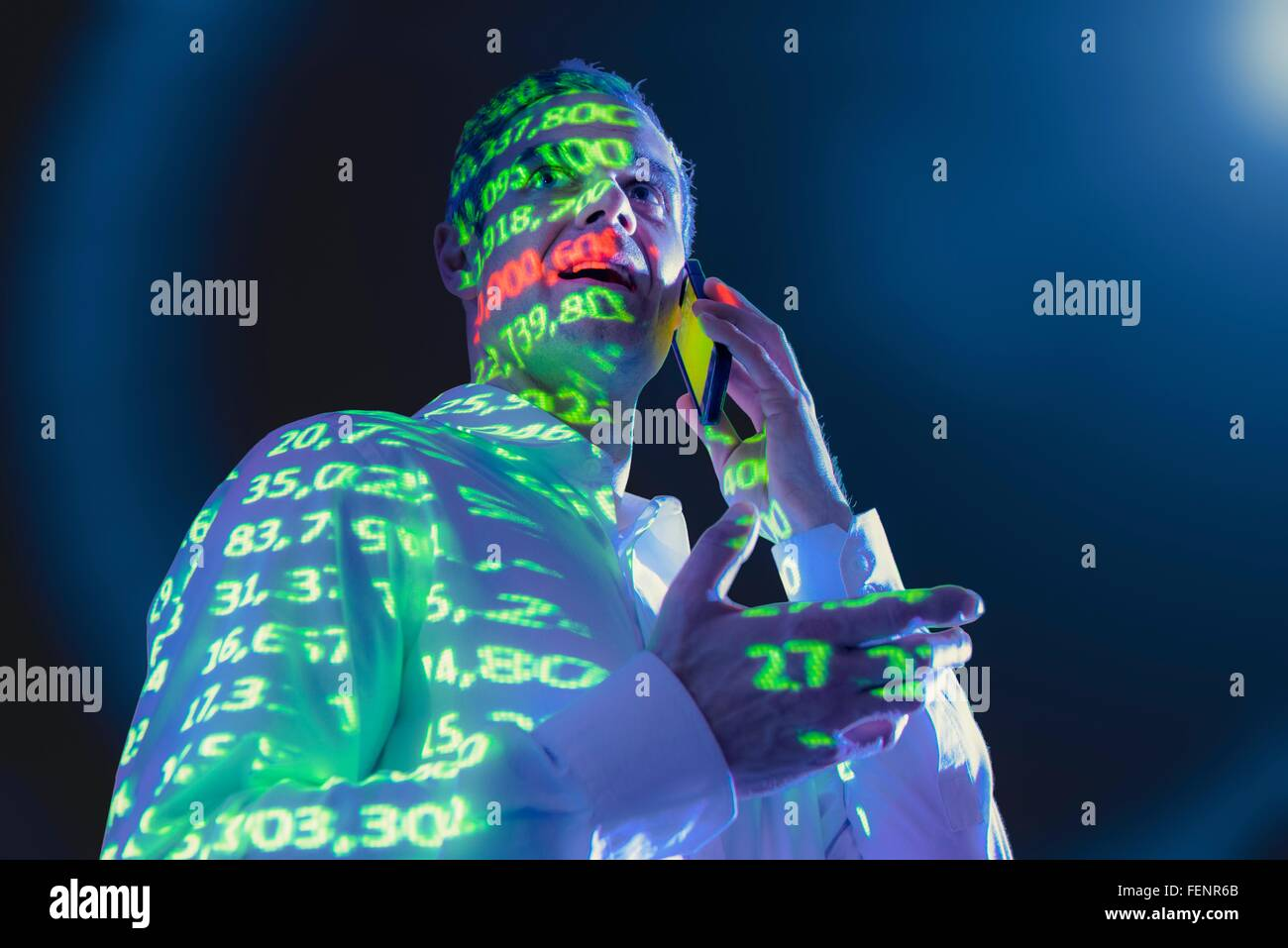 Businessman using mobile phone with projected financial data - Stock Image