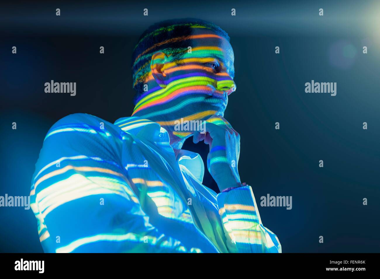 Businessman in thought with projected graphical financial data - Stock Image