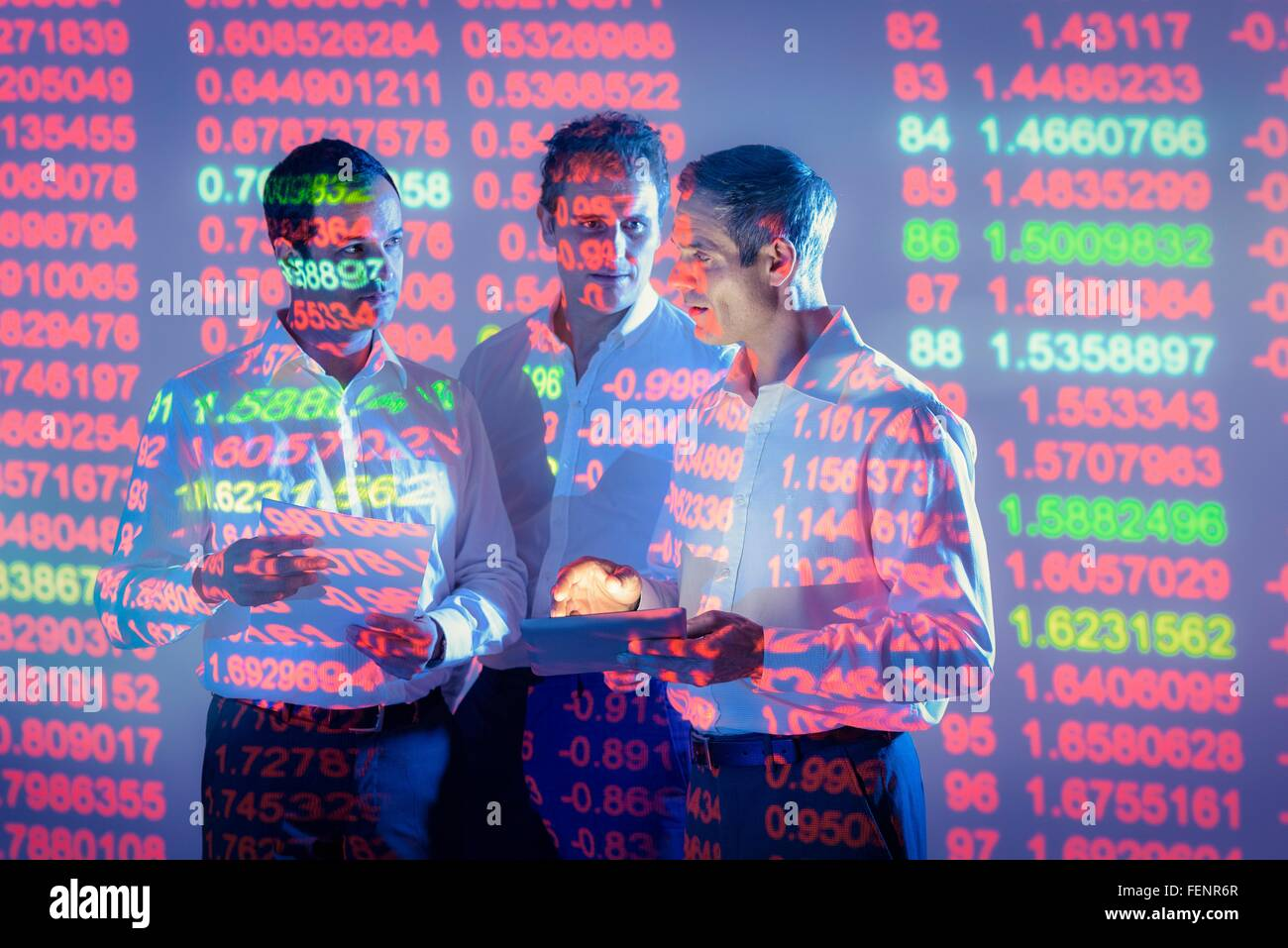 Businessmen in conversation with projected graphical financial data - Stock Image