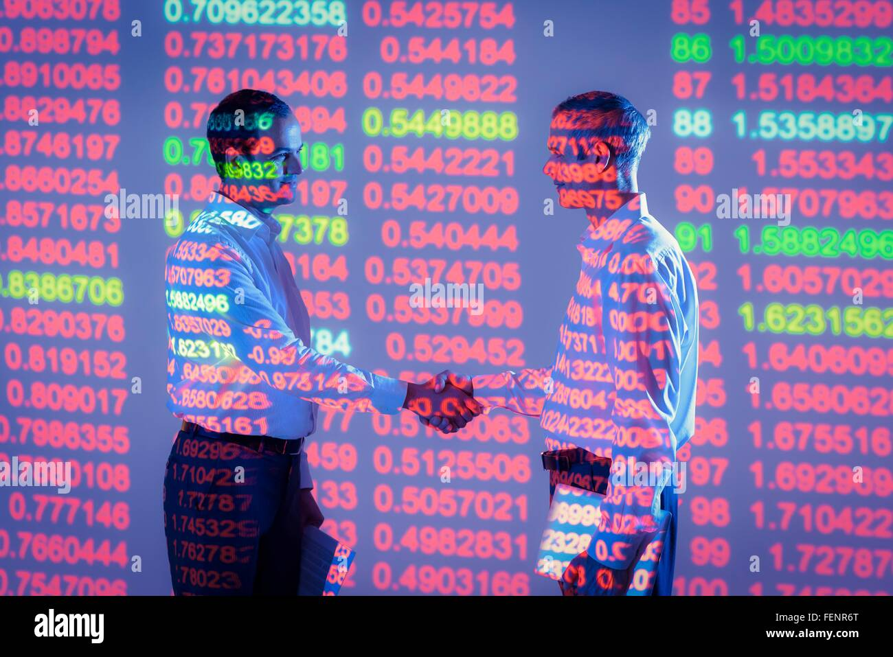 Businessmen shaking hands with projected graphical financial data - Stock Image