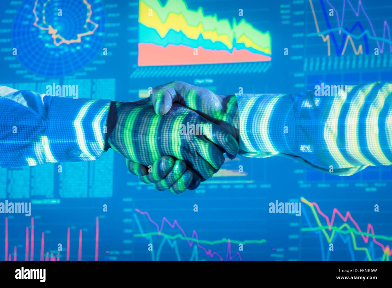 Businessmen shaking hands with projected graphical financial data, close up - Stock Image