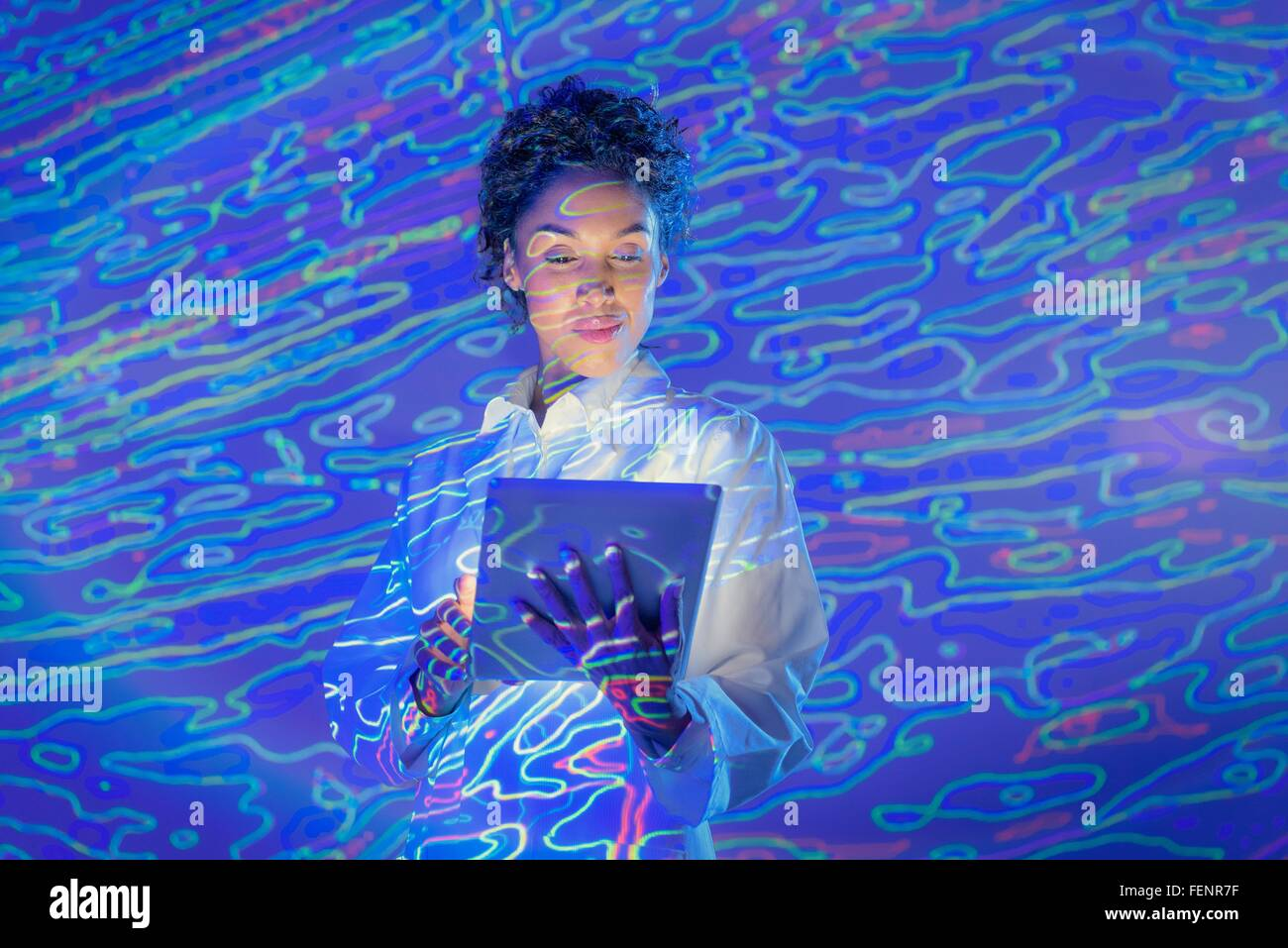 Female scientist with digital tablet and graphical geological data projection - Stock Image