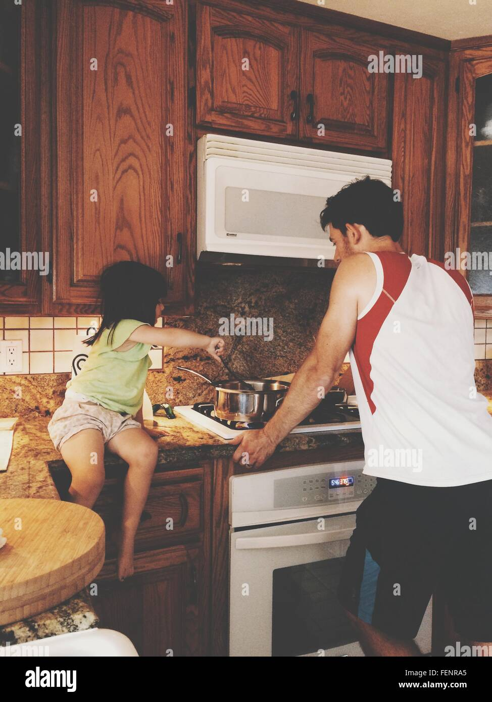 Girl With Father Cooking Food In Kitchen - Stock Image