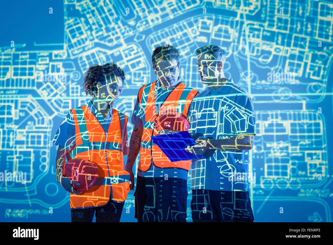 Engineers in discussion with projected plans - Stock Image